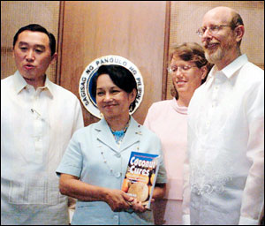 Philippine president Gloria Macapagal-Arroyo with Agriculture Secretary Arthur Yap acknowledges the efforts of author Bruce Fife (with wife Leslie) in dispelling decades of misinformation about coconut and helping revive the coconut industry in the Philippines, which provides for the livelihoods of over 20 million people in that country. Dr. Fife presented president Macapagal-Arroyo with a copy of his new book Coconut Cures.